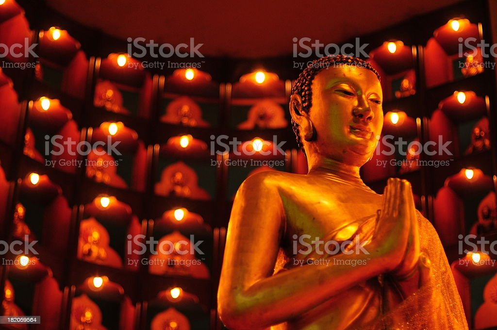 Buddha golden sculpture on lightened gold background stock photo