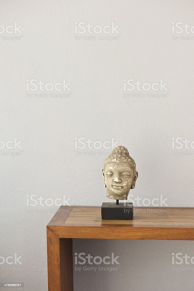 Buddha head in front of a grey wall royalty-free stock photo