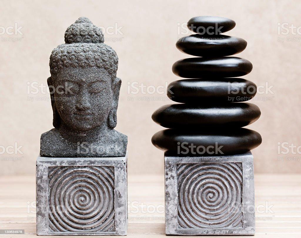 buddha statue beside pile of black basalt pebble stones royalty-free stock photo