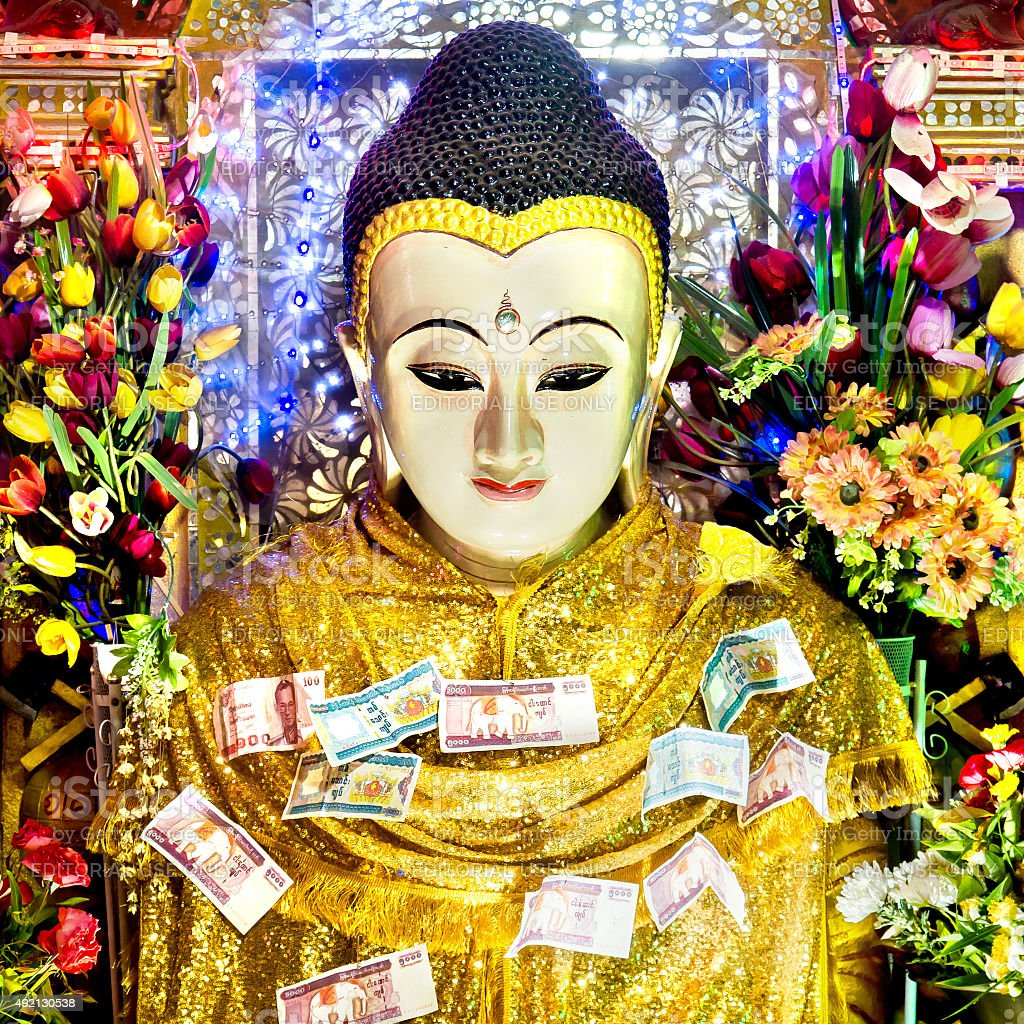 Buddha Statue Covered in Money Offerings at Mount Popa, Myanmar stock photo