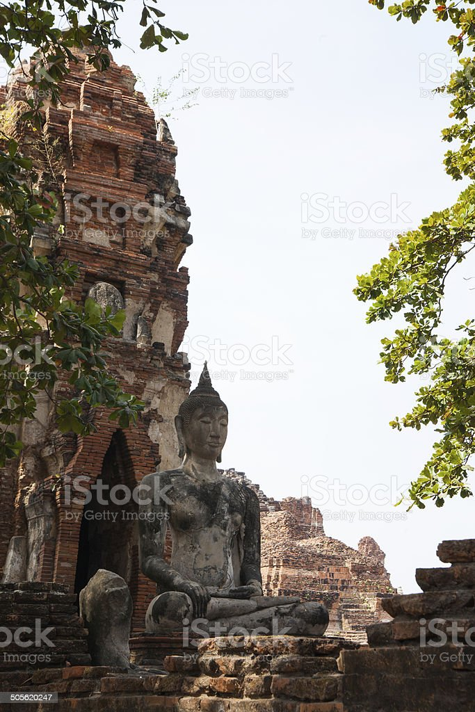 Buddha statue near chedi within Wat Mahathat temple complex stock photo