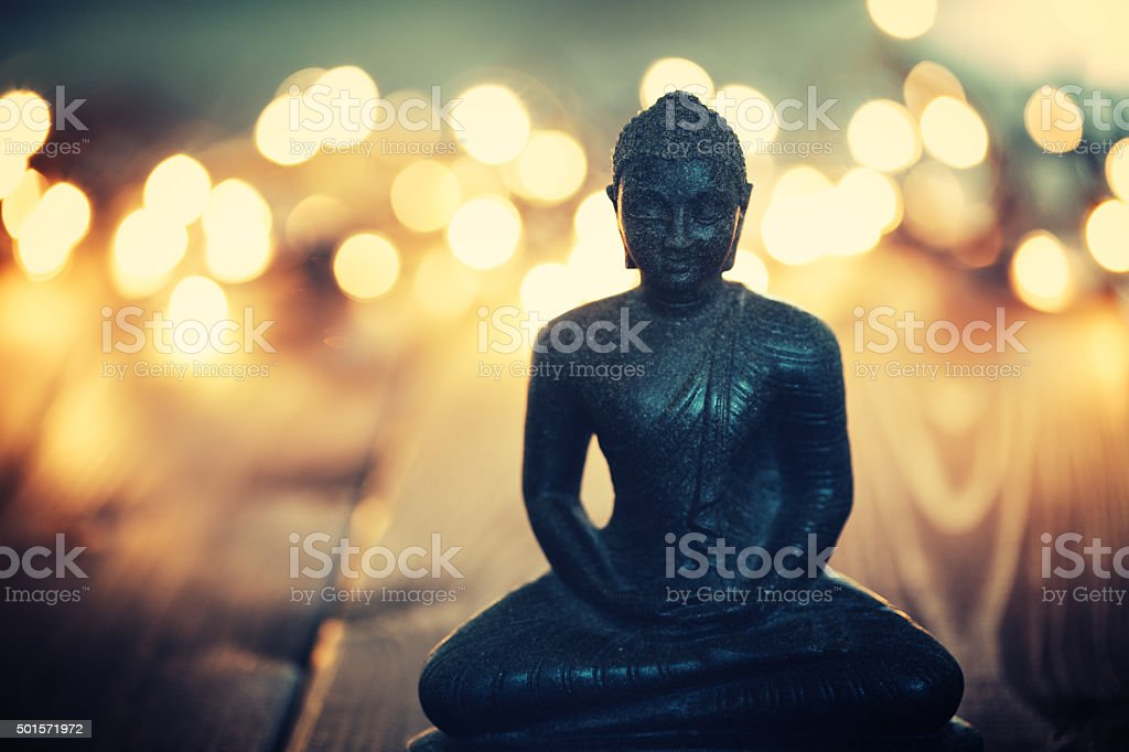 Buddha statue on blurred lights background stock photo