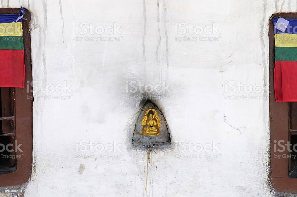Buddha statue placed in concave surface of Buddhist temple wall stock photo