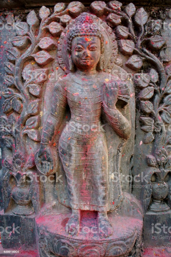 Buddha stone relief  in small street shrine stock photo