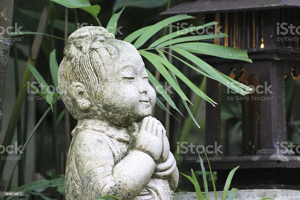 Buddha stone statue in tropical garden royalty-free stock photo