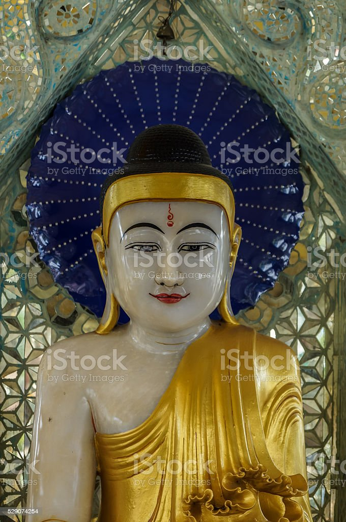 Buddha with blue halo and traditionally painted third eye close-up stock photo