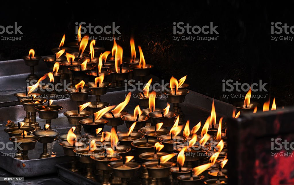 Buddhist butter lamps in Tibetan temple dark stock photo
