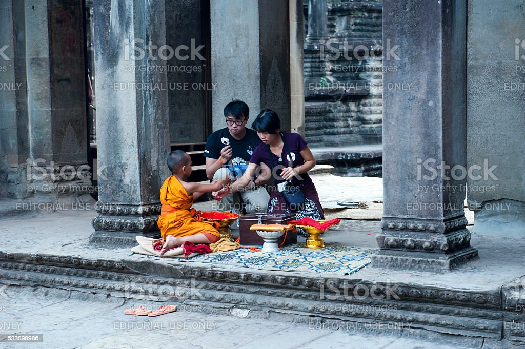 Buddhist child monk ties lucky bracelet to tourists for donation. stock photo