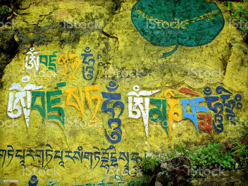 Buddhist encryption on rocks stock photo