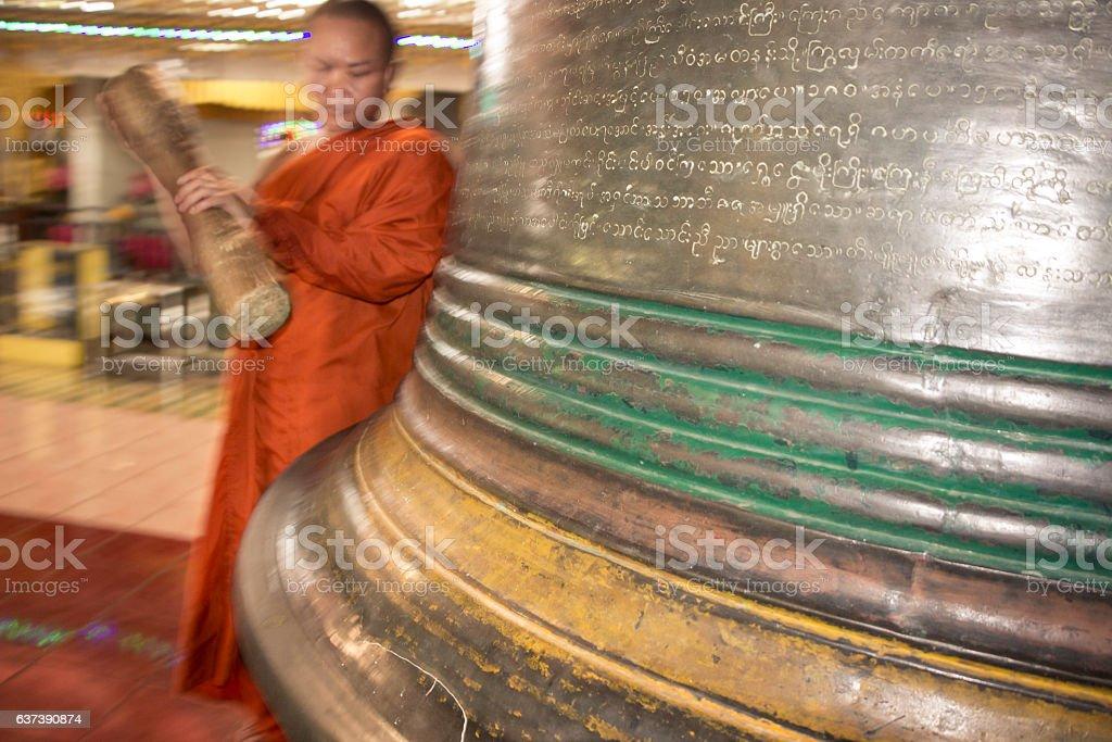 Buddhist hitting the yangon bell in Myanmar stock photo