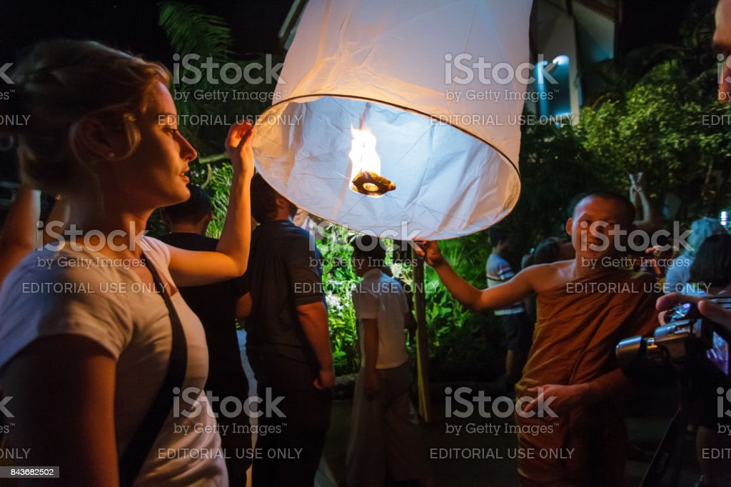 A Buddhist monk and a tourist release a floating lantern in Chiang Mai, Thailand stock photo
