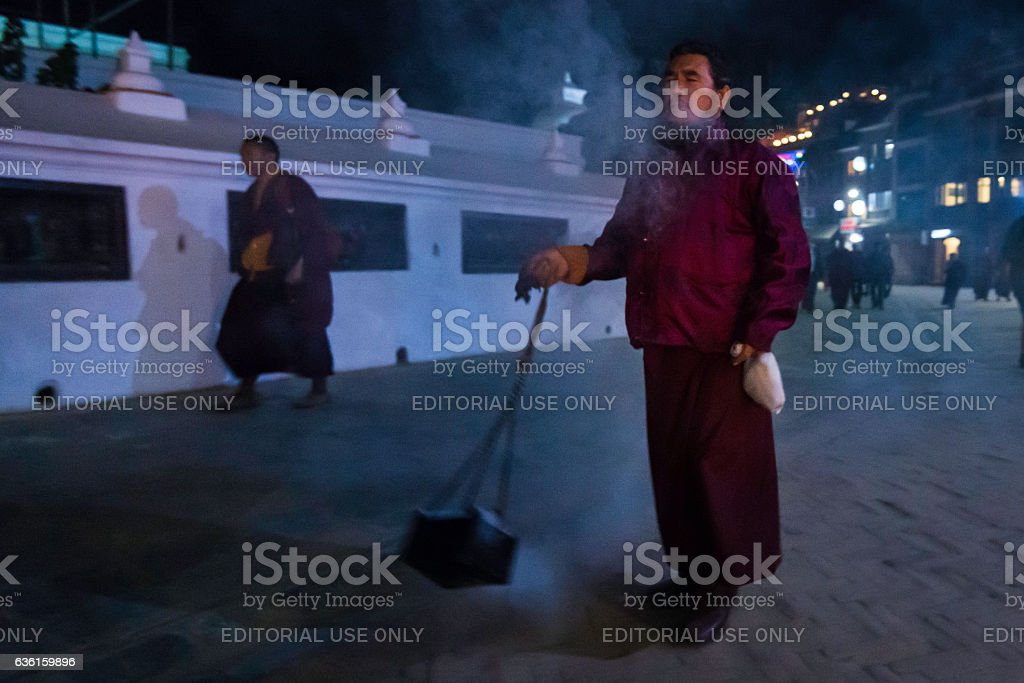 Buddhist monk burning juniper incense Boudhanath temple stupa Kathmandu Nepal stock photo