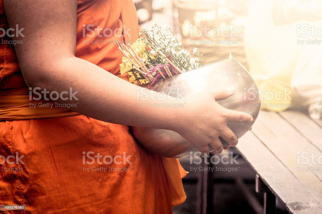 Buddhist monk holding monk's alms bowl stock photo