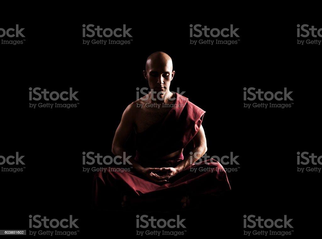 buddhist monk in meditation pose over black background stock photo