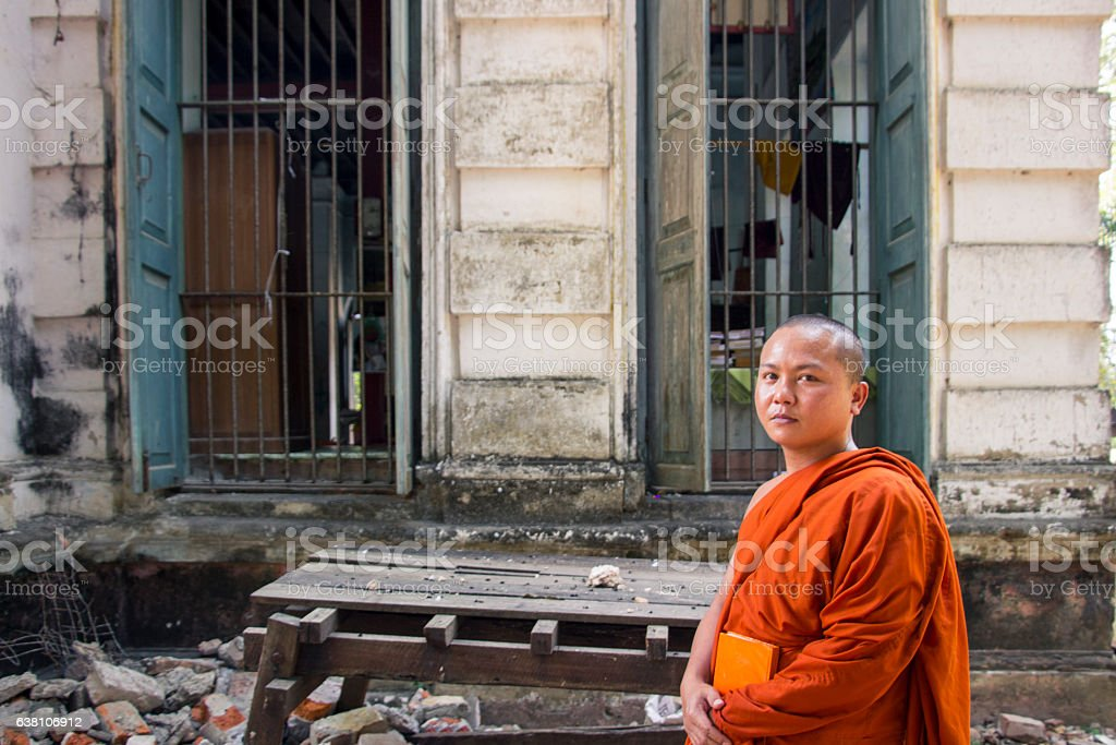 Buddhist monk is walking in front of an old building stock photo