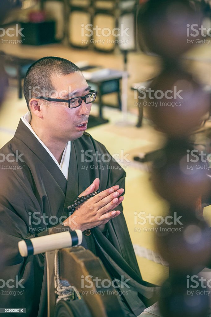 Buddhist monk praying and mala beads stock photo