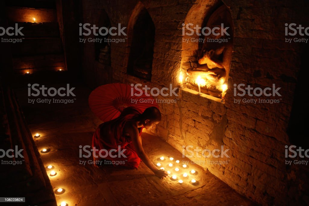 Buddhist monk praying in temple stock photo