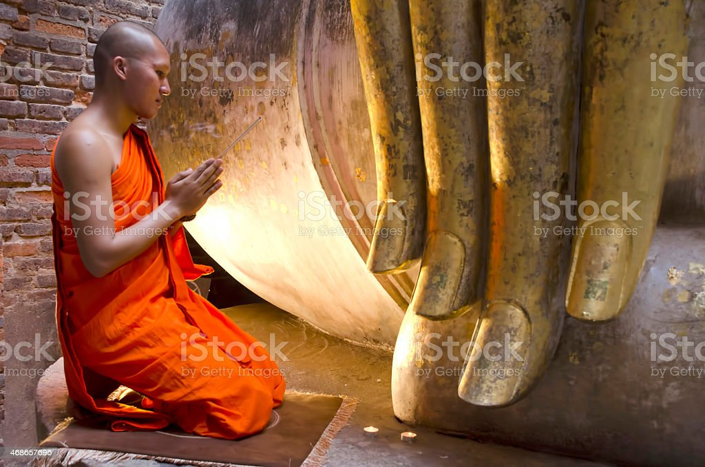 Buddhist monk praying with incense. stock photo