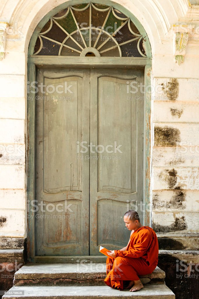 Buddhist  monk reading outside door stock photo