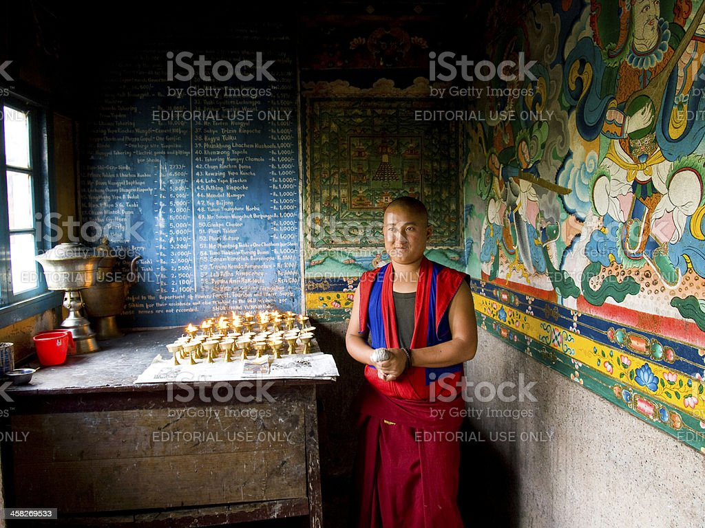 Buddhist monk selling candles in a monastery stock photo