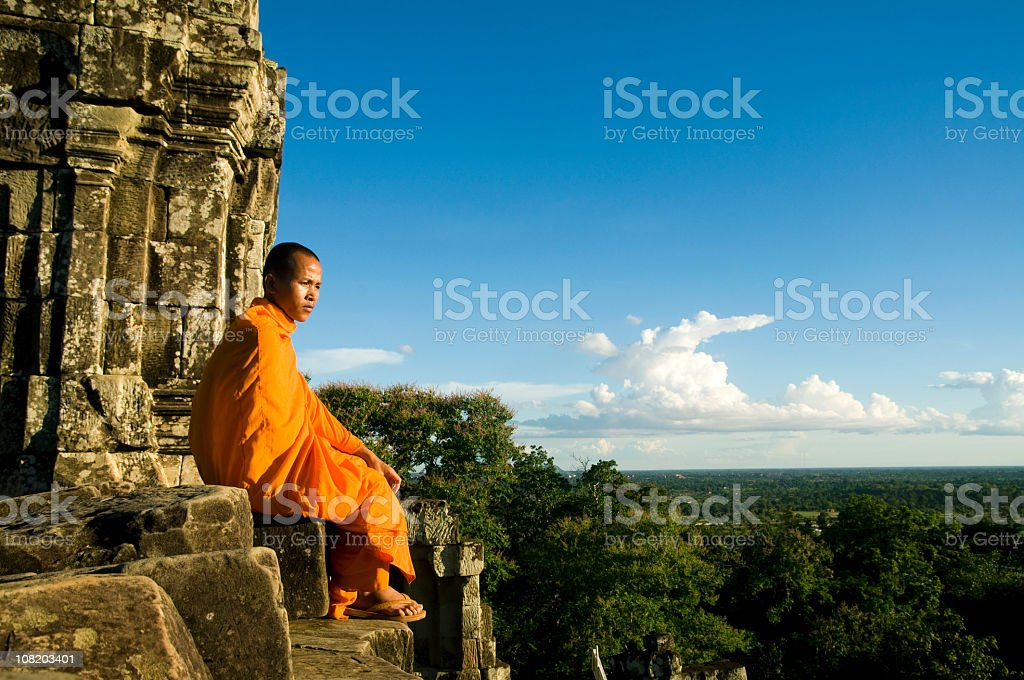 Buddhist monk sitting on a cliff overlooking a valley stock photo