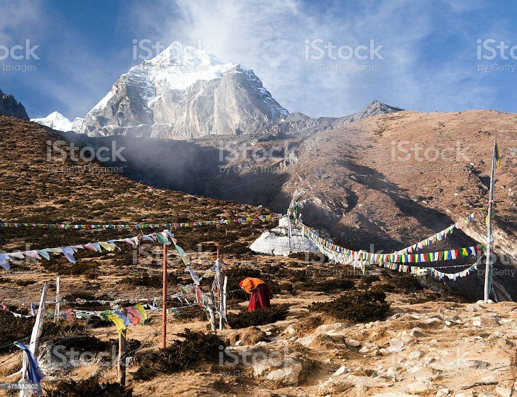 Buddhist monk, stupa and prayer flags near Pangboche monastery stock photo