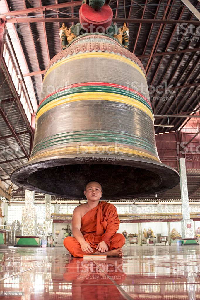 Buddhist monk that  reading a book under the bell stock photo