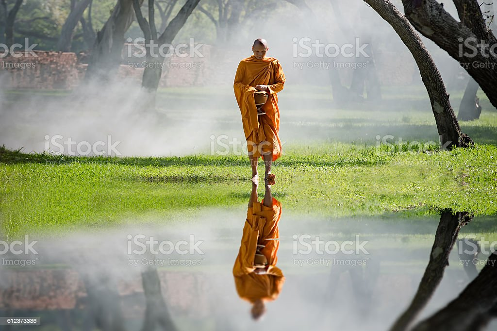 Buddhist Monk walking to receive food stock photo