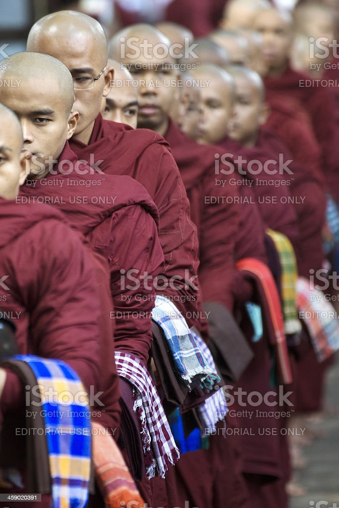 Buddhist monks in line, holding bowls and waiting for food. royalty-free stock photo