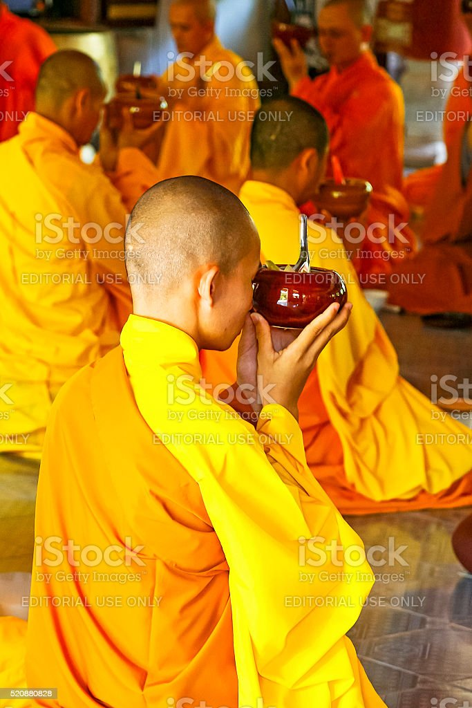Buddhist monks in monastery at prayer before meal stock photo