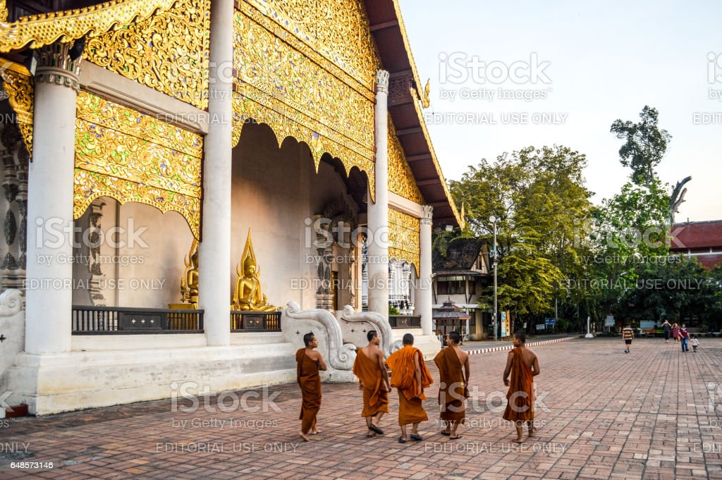 Buddhist monks outside ancient temple stock photo