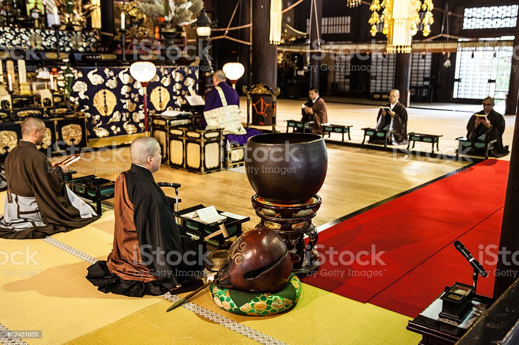 Buddhist monks praying in early morning inside a Temple stock photo