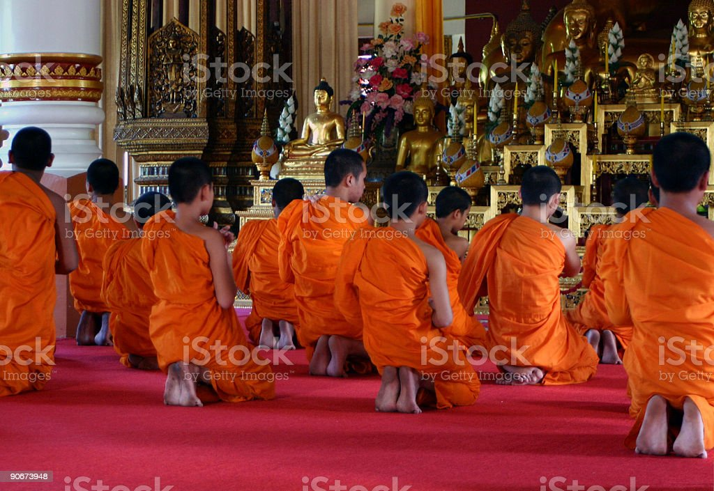 Buddhist monks praying in Thai temple. stock photo