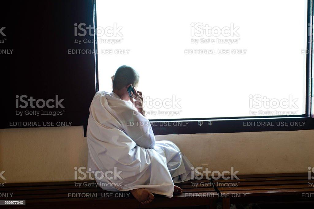 Buddhist nun talking on mobile phone, Bangkok, Thailand stock photo