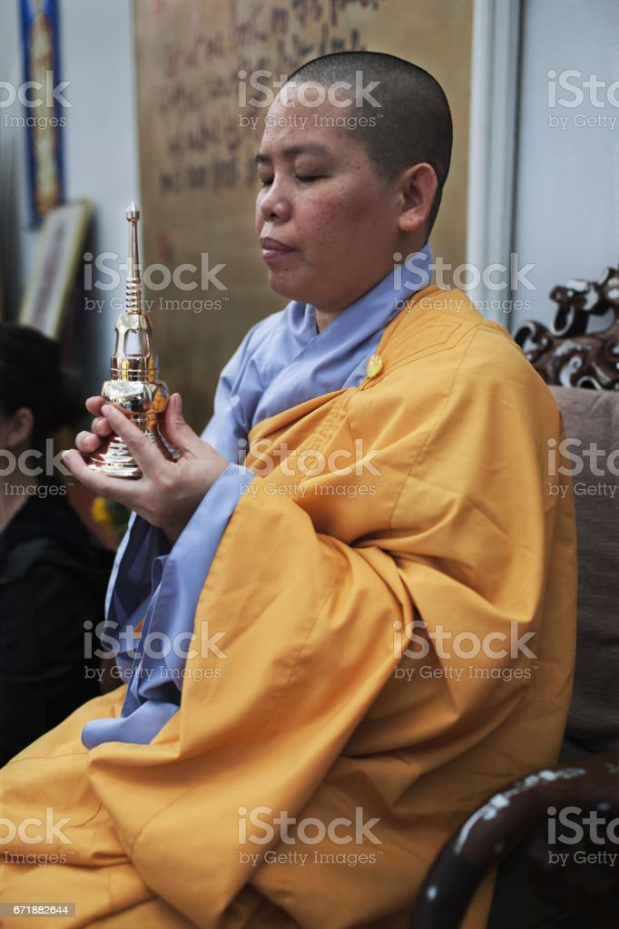 Buddhist nun with a shaved head wearing a yellow robe praying inside a temple stock photo