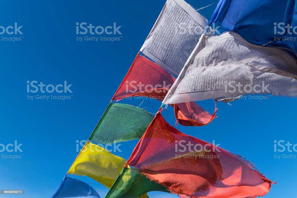 Buddhist Prayer Flags with blue sky on background in India stock photo