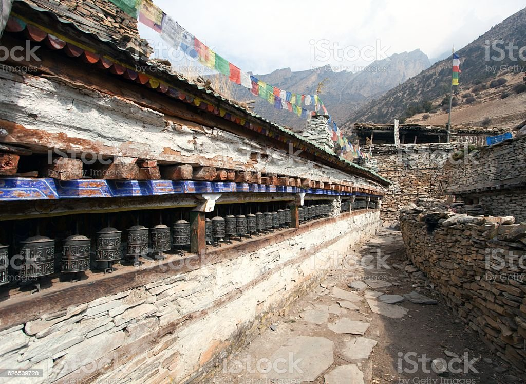 Buddhist prayer many wall with prayer wheels in nepalese village stock photo
