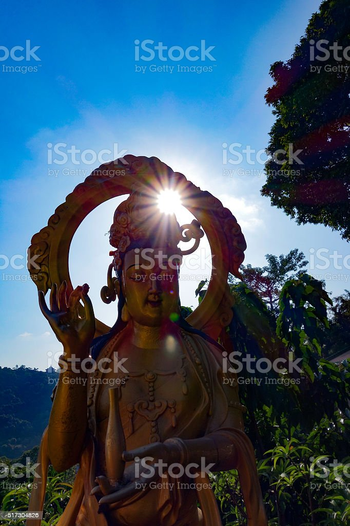 Buddhist Statue with Sun Flare stock photo