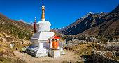 Buddhist stupa and prayer wheel on Himalayan mountain trail Nepal