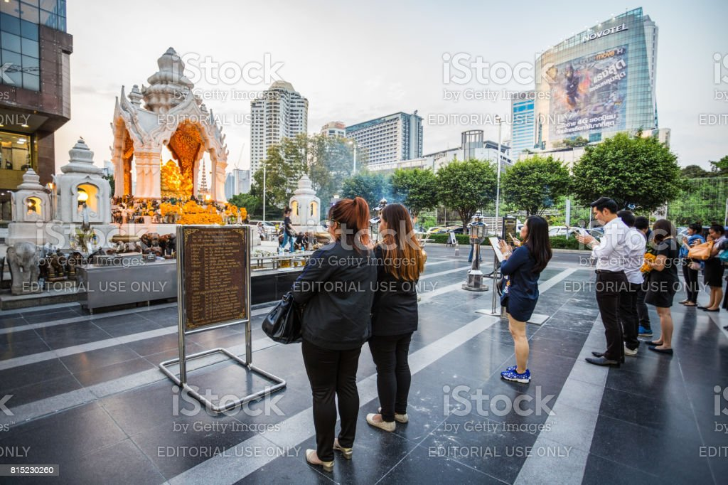 BANGKOK THAILAND MARCH 01, 2017 - Buddisit faithful pray on Trimurti Shrine, located in front of Central World, is known as God of Love, granting happiness in romance. stock photo