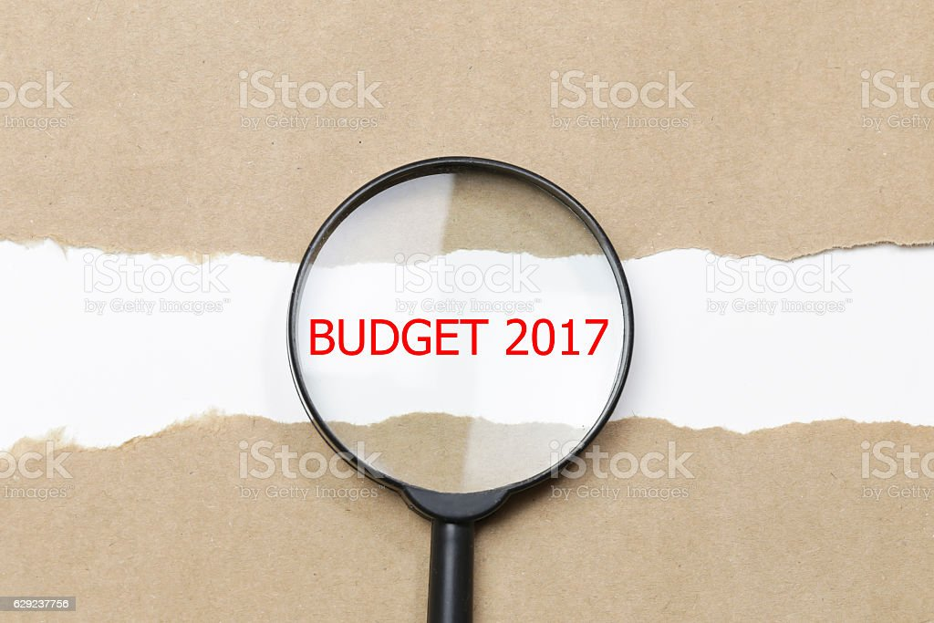 Budget 2017 word written under torn paper with magnifying glass stock photo