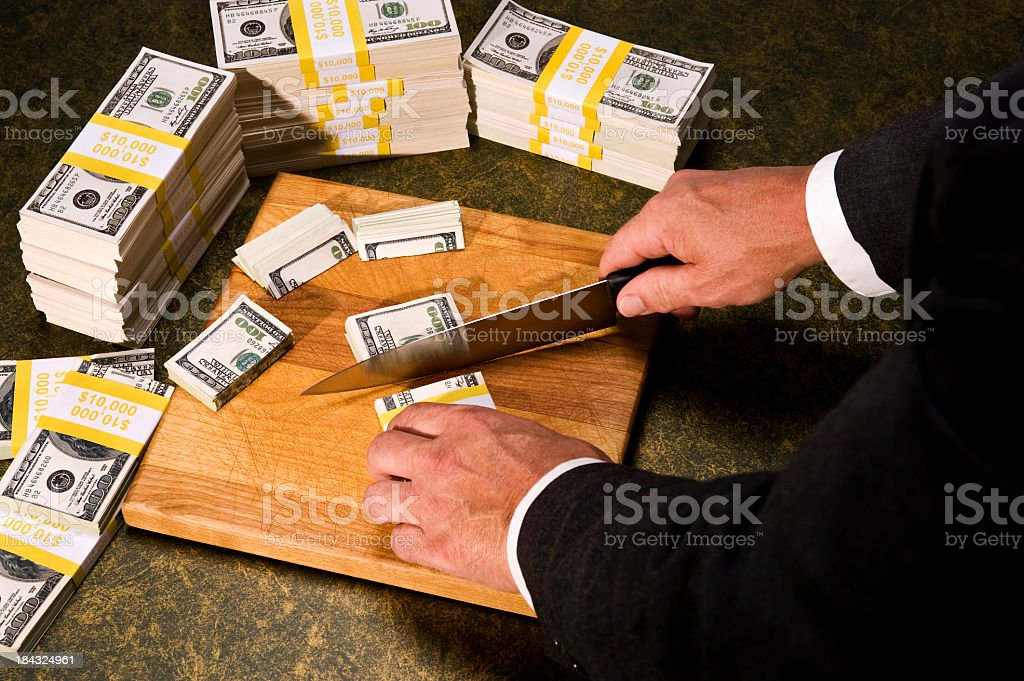 Budget Cutting - Congressman cutting stacks of money stock photo