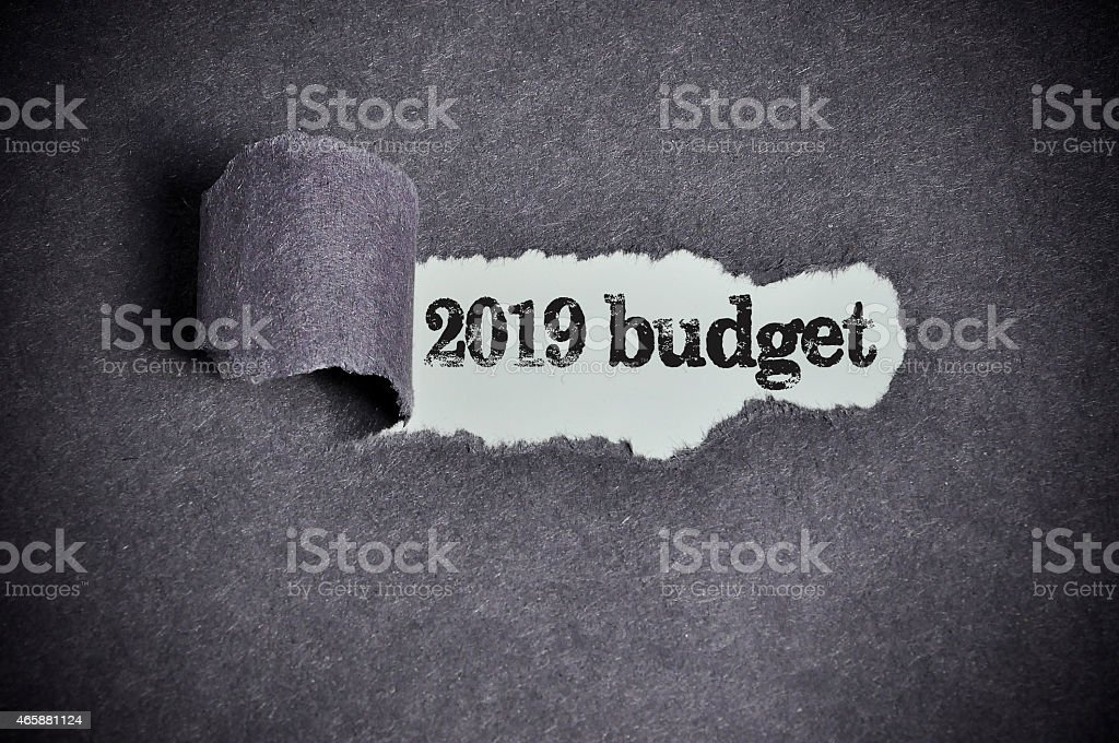2019 budget word under torn black sugar paper stock photo