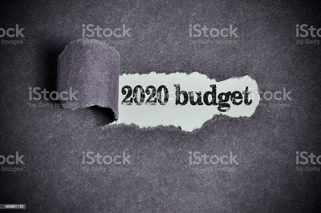 2020 budget word under torn black sugar paper stock photo