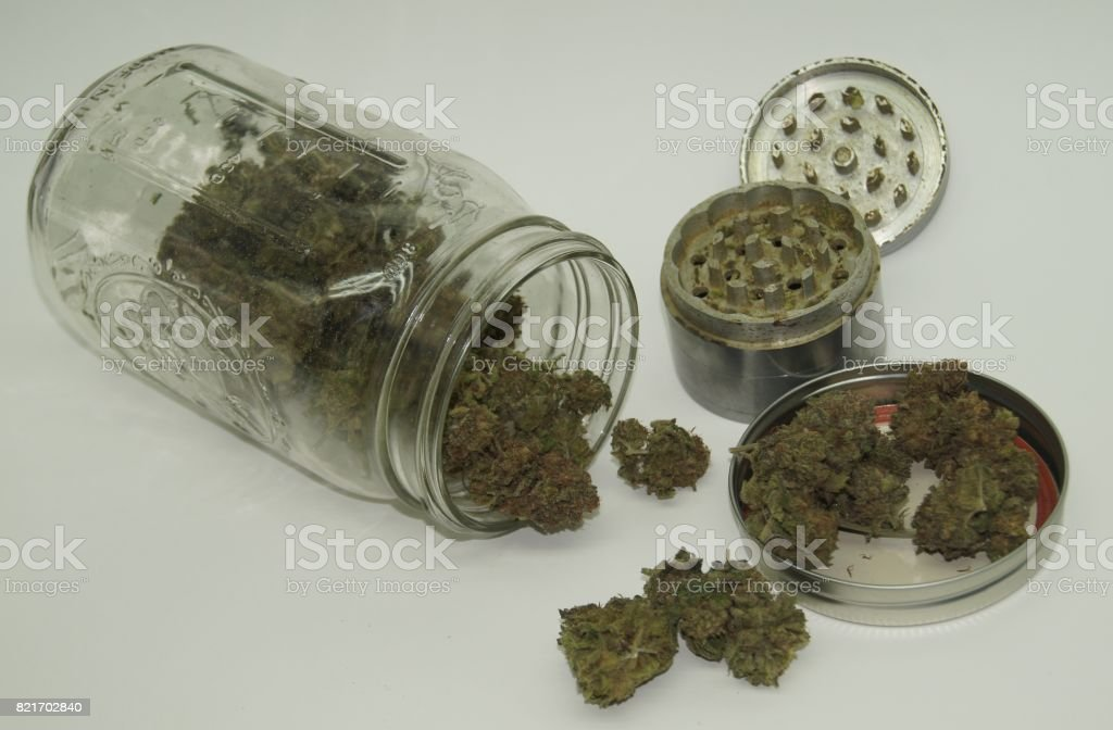 Buds of Cannabis Displayed with Mason Jar and Herb Grinder stock photo