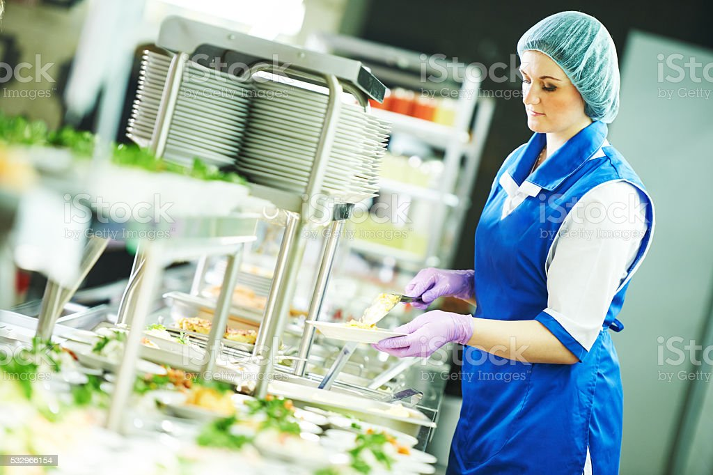 buffet female worker servicing food in cafeteria stock photo