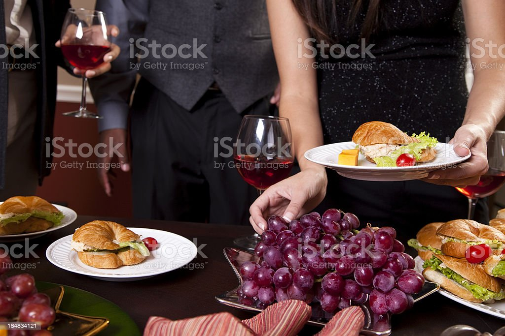 Buffet table. Appetizers, snacks. People eat holiday sandwiches. Wine. Party. stock photo