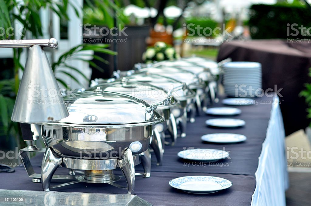 Buffet table with plates and silver serving trays stock photo