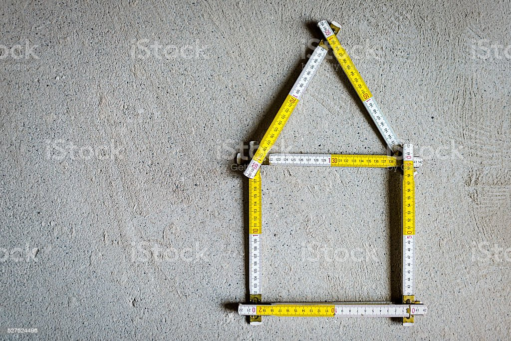 Buiding ruler in shape of house on concret floor stock photo
