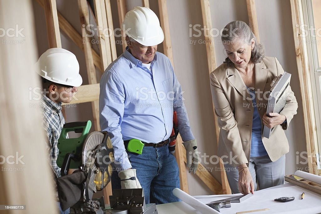 Builder and construction team discussing building plans royalty-free stock photo